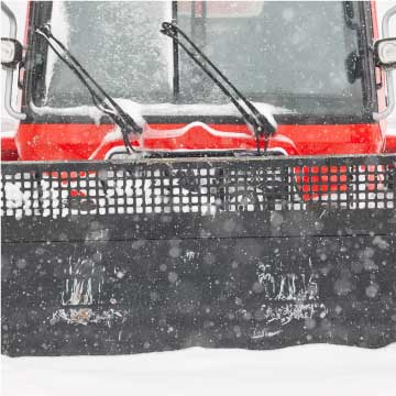 Snow clearing tractor with black plow on front