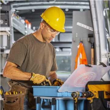 Man in yellow hard hat working behind organized work van
