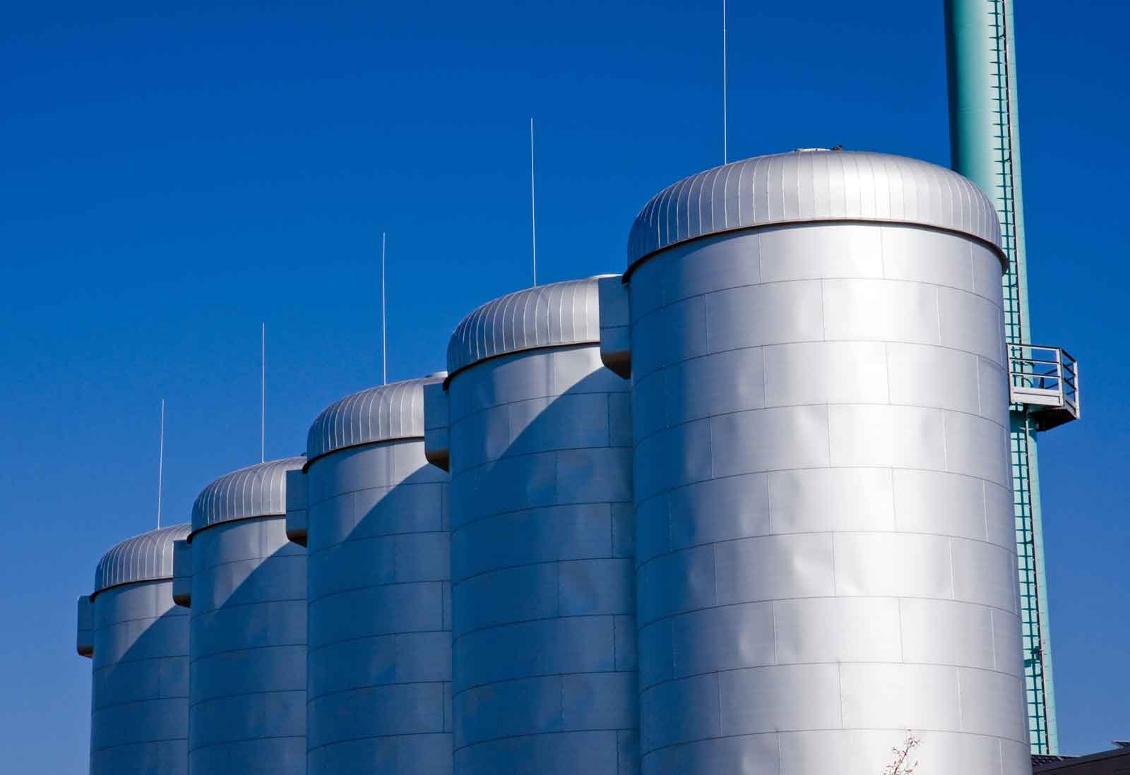 A row of four silver metal silos against a blue sky