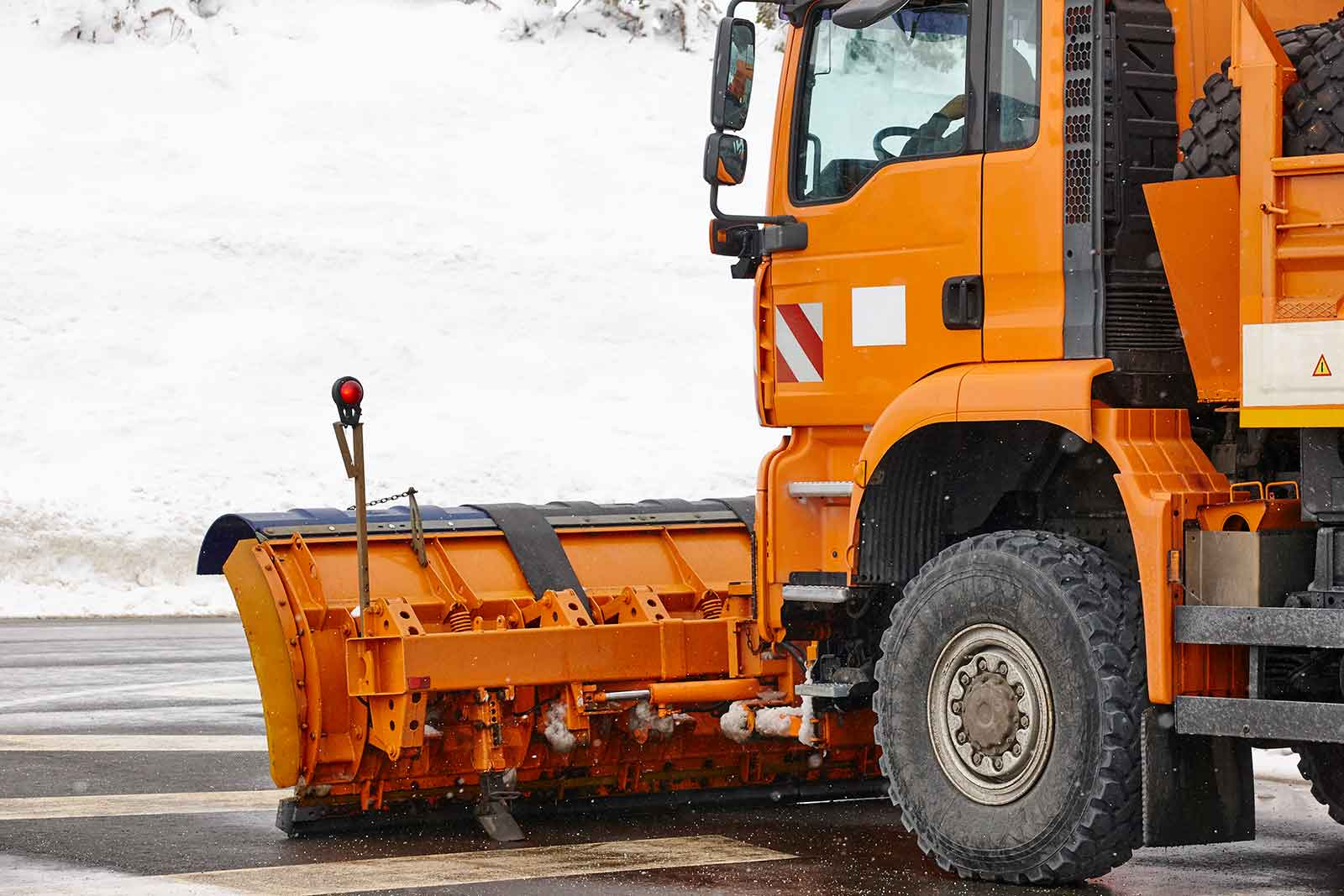 Orange plow on organge truck on road in front of snow