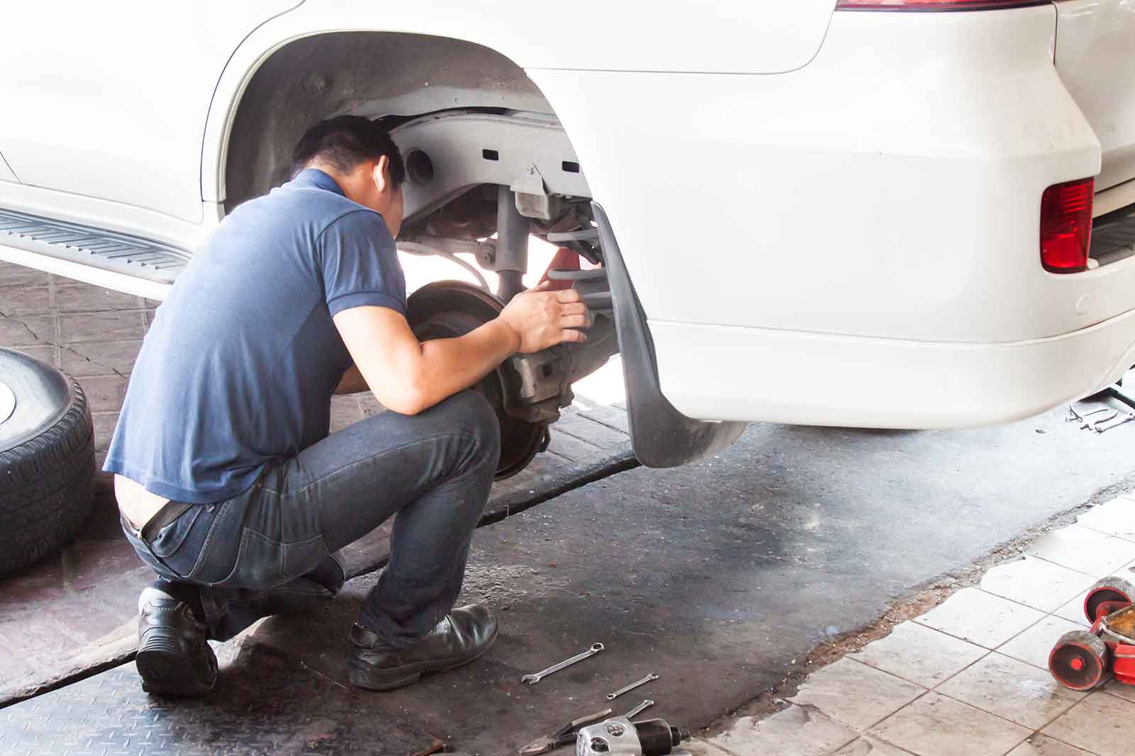 Suspension and brakes inspection of van by male mechanic in blue shirt and jeans