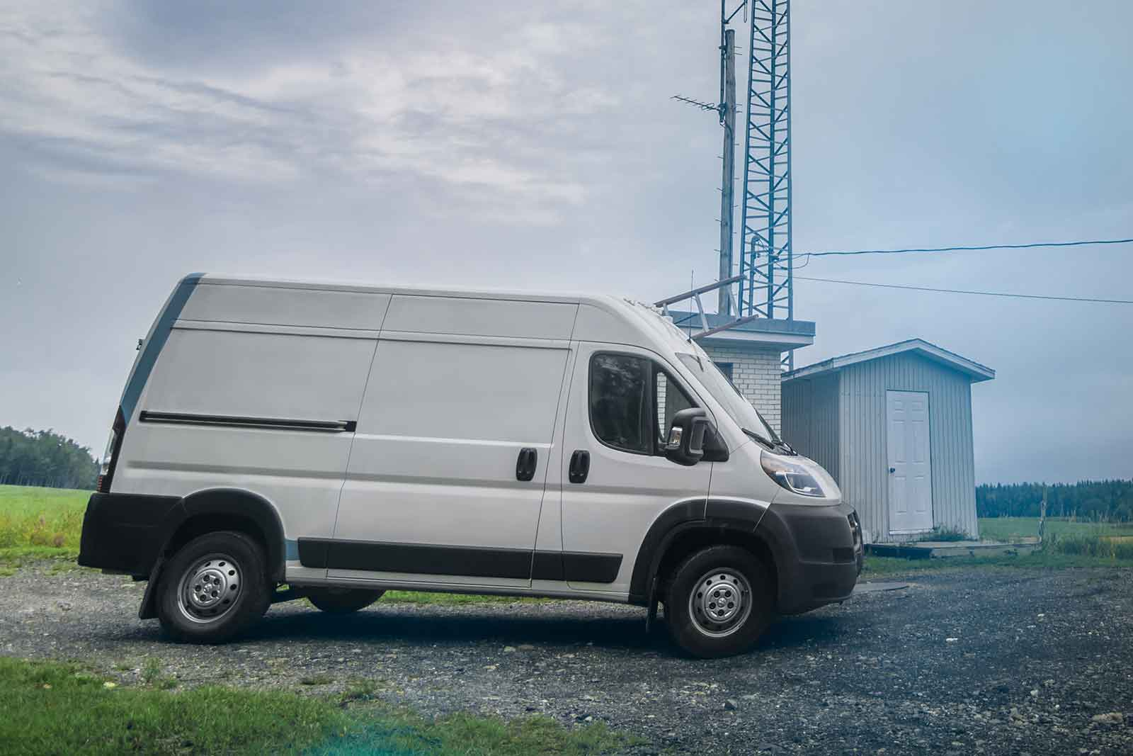 White work van on unpaved road in front of small building and power tower