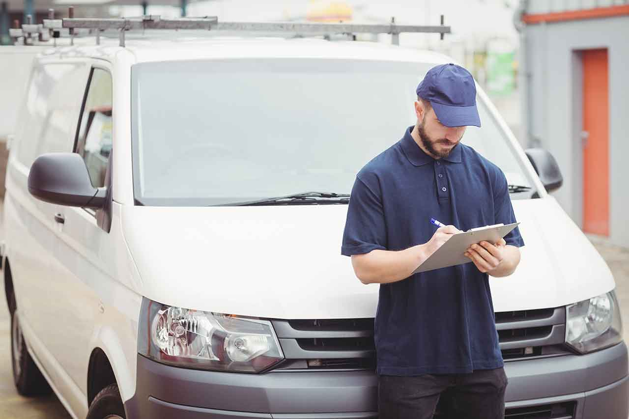 Man in blue shirt and blue hat standing in front of white cargo van with upfitting roof rack writing on a clip board