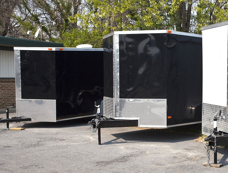 Three enclosed cargo trailers side by side two black and silver and one white on concrete