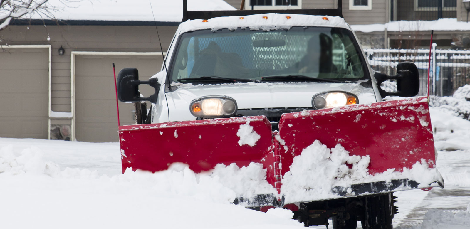 Red plow on white truck in snow in front of a building