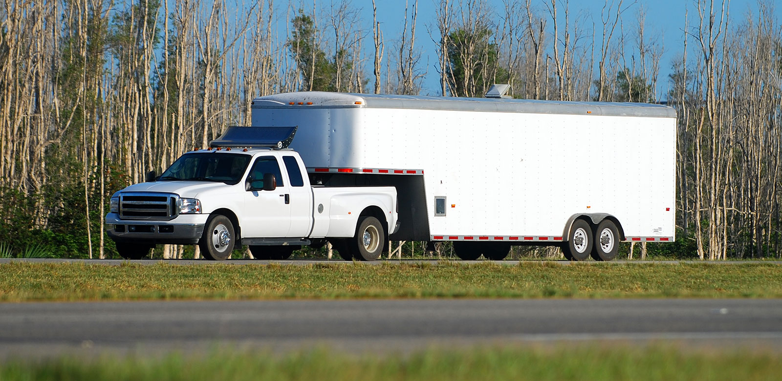 Large white pick up truck trailer being hauled by white pick up truck