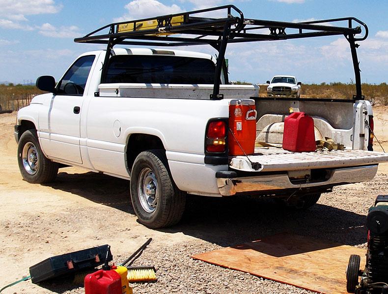 Black ladder rack on white work truck on gravel road